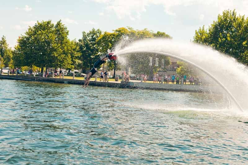 Doing a Flyboarding dolphin dive for a crowd in downtown Kelowna by the sails